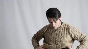 Όμορφος κατάλληλος νεαρός άνδρας που ντύνει στο στούντιο απόθεμα βίντεο