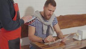 Όμορφος νέος τύπος που διατάζει τα τρόφιμα σε έναν καφέ απόθεμα βίντεο