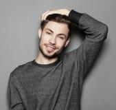 Όμορφος νεαρός άνδρας στην έξυπνη περιστασιακή ένδυση που εξετάζει τη κάμερα στοκ φωτογραφία