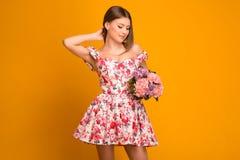 Όμορφος ξανθός με μια ανθοδέσμη των λουλουδιών σε ένα φόρεμα στοκ εικόνα