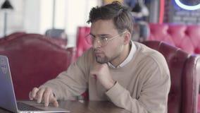 Όμορφος σκεπτικός νεαρός άνδρας με τα γυαλιά που εξετάζει ένα lap-top καθμένος σε έναν πίνακα σε έναν καφέ ή ένα εστιατόριο φιλμ μικρού μήκους