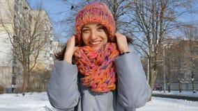 Όμορφο ενήλικο κορίτσι στο θερμό παλτό και το ζωηρόχρωμο πλεκτό καπέλο και μαντίλι που έχει τη διασκέδαση υπαίθρια κατά τη διάρκε απόθεμα βίντεο