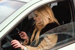 Όμορφο ευτυχές κορίτσι στο αυτοκίνητο που χρησιμοποιεί το smartphone της στοκ φωτογραφία