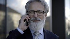Όμορφο καυκάσιο ανώτερο CEO που χρησιμοποιεί ένα smartphone και μια έξυπνη ταμπλέτα φιλμ μικρού μήκους