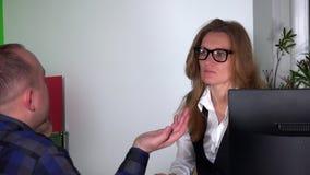 Όμορφο κορίτσι αρχιτεκτόνων με τα γυαλιά που συσκέπτεται το άτομο πελατών με τον υπολογιστή ταμπλετών φιλμ μικρού μήκους