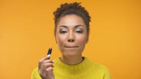 Όμορφο κορίτσι αφροαμερικάνων που εφαρμόζει το κραγιόν και το κλείσιμο του ματιού, έτοιμα για την ημερομηνία απόθεμα βίντεο