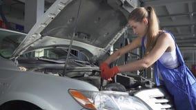 Όμορφο κορίτσι στις ομοιόμορφες στροφές ένα κατσαβίδι σε μια μηχανή αυτοκινήτων Υπηρεσία αυτοκινήτων, επισκευή, συντήρηση και ένν απόθεμα βίντεο