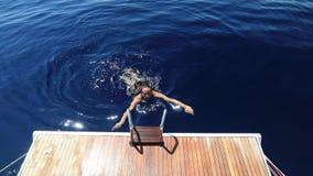 Όμορφο κορίτσι που κολυμπά κοντά στο γιοτ φιλμ μικρού μήκους