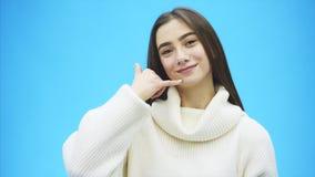 Όμορφο νέο κορίτσι σε ένα μπλε υπόβαθρο Το κορίτσι παρουσιάζει τηλεφώνημα με μια χειρονομία Ντυμένος σε ένα άσπρο θερμό πουλόβερ απόθεμα βίντεο