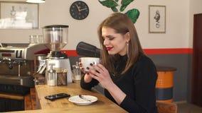 Όμορφο νέο κορίτσι που απολαμβάνει ένα cappuccino σε έναν καφέ απόθεμα βίντεο