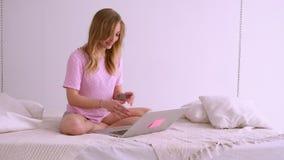 Όμορφο ξανθό κορίτσι σε μια ρόδινη μπλούζα της ευρωπαϊκής συνεδρίασης εμφάνισης στο κρεβάτι με ένα lap-top Εργάζεται στο σπίτι ch απόθεμα βίντεο