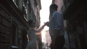 Όμορφο ρομαντικό γαμήλιο ζεύγος του νεόνυμφου και της νύφης στα πανέμορφα χέρια εκμετάλλευσης φορεμάτων περπατώντας την παλαιά οδ απόθεμα βίντεο