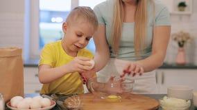 Όμορφο caucsian παιδί με τα μπλε μάτια που ψήνει προετοιμάζοντας το κέικ Νέα διδασκαλία γυναικών μητέρων που παρουσιάζει στο παιδ απόθεμα βίντεο