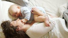 Ώριμα παιχνίδια μητέρων με το μωρό που βρίσκεται στο κρεβάτι Το παιδί αγγίζει το δάχτυλό του στο στόμα της μητέρας, η ανάπτυξη απόθεμα βίντεο