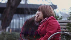 Ώριμες γυναίκα και αυτή μεγαλωμένη συνεδρίαση κορών σε έναν πάγκο στο πάρκο και τη συζήτηση πόλεων Θερμή σχέση Μητέρα ` s φιλμ μικρού μήκους