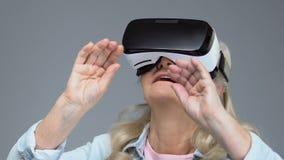 Ώριμη γυναίκα που φορά την κάσκα εικονικής πραγματικότητας, συσκευή ψυχαγωγίας, καινοτομία απόθεμα βίντεο