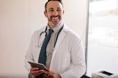 Ώριμος αρσενικός γιατρός με μια ψηφιακή ταμπλέτα στο γραφείο του στοκ φωτογραφία με δικαίωμα ελεύθερης χρήσης
