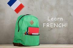 σακίδιο πλάτης, σημαία της Γαλλίας και σχολικές προμήθειες ενάντια σε έναν τοίχο τσιμέντου με το texh & x22 Μάθετε τα γαλλικά στοκ εικόνα με δικαίωμα ελεύθερης χρήσης