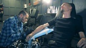 Σαλόνι δερματοστιξιών με ένα με ειδικές ανάγκες άτομο που παίρνει μια δερματοστιξία στην πρόσθεσή του απόθεμα βίντεο