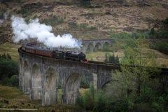 Σαφές τραίνο ατμού Jacobite Hogwarts στην οδογέφυρα Glenfinnan στη Σκωτία στοκ εικόνα