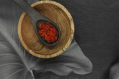 Σαφράνι στο μαύρο ξύλινο κουτάλι στο μαύρο υπόβαθρο πετρών στοκ φωτογραφίες