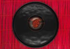 Σαφράνι στο μαύρο ξύλινο κύπελλο στο κόκκινο χαλί μπαμπού στοκ φωτογραφία