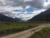 Σειρά βουνών με τα δάση και το ρεύμα Πολύβλαστο συγκρατημένο τροπικό δάσος στην Αλάσκα με τα σύννεφα και τον ήλιο στοκ φωτογραφία