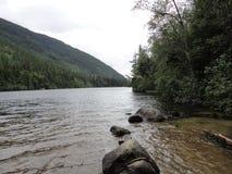 Σειρά βουνών με τα δάση και το ρεύμα Πολύβλαστο συγκρατημένο τροπικό δάσος στην Αλάσκα με τα σύννεφα και τον ήλιο στοκ φωτογραφίες με δικαίωμα ελεύθερης χρήσης