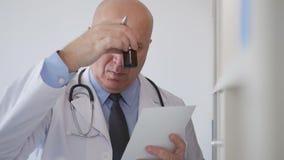 Σε αργή κίνηση με το κοίταγμα γιατρών σε έναν παραλήπτη φαρμάκων και σε μια συνταγή απόθεμα βίντεο