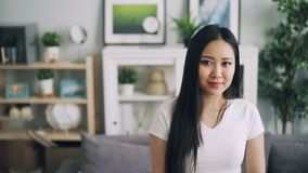 Σε αργή κίνηση πορτρέτο της λατρευτής ασιατικής κυρίας με το όμορφο χαμόγελο που στέκεται στο συμπαθητικό δωμάτιο, που χαμογελά κ απόθεμα βίντεο