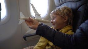 Σε αργή κίνηση πυροβολισμός ενός μικρού αγοριού που παίζει με την άσπρη συνεδρίαση αεροπλάνων παιχνιδιών σε μια καρέκλα εν πλω εν απόθεμα βίντεο