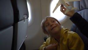 Σε αργή κίνηση πυροβολισμός ενός μικρού αγοριού που παίζει με την άσπρη συνεδρίαση αεροπλάνων παιχνιδιών σε μια καρέκλα εν πλω εν φιλμ μικρού μήκους