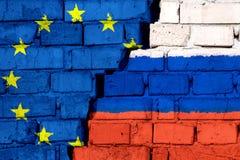 Σημαίες της ΕΕ της Ευρωπαϊκής Ένωσης και της Ρωσίας στο τουβλότοιχο με τη μεγάλη ρωγμή στη μέση απεικόνιση αποθεμάτων