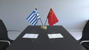 Σημαίες της Ελλάδας και της Κίνας και έγγραφα για τον πίνακα Διαπραγματεύσεις και υπογραφή μιας διεθνούς συμφωνίας Εννοιολογικός  απεικόνιση αποθεμάτων