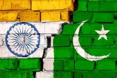 Σημαίες της Ινδίας και του Πακιστάν στο τουβλότοιχο με τη μεγάλη ρωγμή στη μέση Σύμβολο των προβλημάτων μεταξύ των χωρών ελεύθερη απεικόνιση δικαιώματος