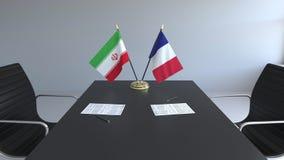 Σημαίες του Ιράν και της Γαλλίας και έγγραφα για τον πίνακα Διαπραγματεύσεις και υπογραφή μιας διεθνούς συμφωνίας Εννοιολογικός τ απεικόνιση αποθεμάτων