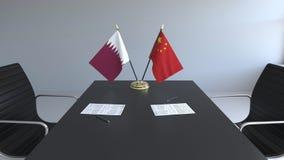 Σημαίες του Κατάρ και της Κίνας και έγγραφα για τον πίνακα Διαπραγματεύσεις και υπογραφή μιας διεθνούς συμφωνίας Εννοιολογικός τρ ελεύθερη απεικόνιση δικαιώματος