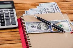 Σημειωματάριο, μάνδρα, δολάρια και ένας υπολογιστής σε ένα ξύλινο υπόβαθρο στοκ φωτογραφία με δικαίωμα ελεύθερης χρήσης