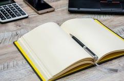Σημειωματάριο, μάνδρα, smartphone και μέρος του lap-top σε ένα ξύλινο υπόβαθρο στοκ εικόνες