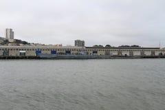 Σκάφος που επιπλέει μπροστά από την πόλη στην άκρη του ωκεανού στοκ εικόνα