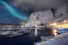 Σκανδιναβικός του χωριού φωτισμός με τα βόρεια φω'τα που λάμπουν στο βουνό χιονιού στοκ φωτογραφία με δικαίωμα ελεύθερης χρήσης