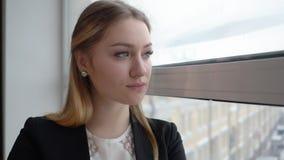 Σκεπτική γυναίκα στο επιχειρησιακό κοστούμι που κοιτάζει στο παράθυρο γραφείων Έννοια επιχειρηματιών απόθεμα βίντεο