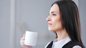 Σκεπτική κομψή επιχειρηματίας κινηματογραφήσεων σε πρώτο πλάνο που απολαμβάνει πίνοντας το καυτό ποτό από την άσπρη κούπα απόθεμα βίντεο