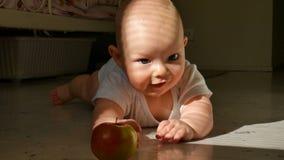 Σκηνή ενός όμορφου φαλακρού μικρού παιδιού που βρίσκεται στο πάτωμα με το πράσινο μήλο απόθεμα βίντεο