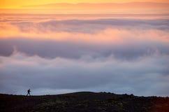 Σκιαγραφία ενός ατόμου στην κορυφογραμμή επάνω από τη θάλασσα των σύννεφων, misty βουνά στο ηλιοβασίλεμα στην Ισλανδία στοκ εικόνες με δικαίωμα ελεύθερης χρήσης