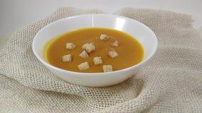 Σκληρά chuks σούπας κολοκύθας που περιέρχονται στο άσπρο πιάτο φιλμ μικρού μήκους