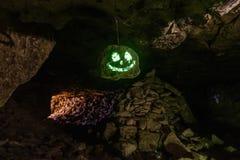 Σκοτεινό ανατριχιαστικό καμμένος φωσφορίζον πρόσωπο χαμόγελου στην ένωση της πέτρας στη σπηλιά στοκ εικόνες