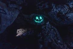 Σκοτεινό ανατριχιαστικό καμμένος φωσφορίζον πρόσωπο χαμόγελου στην ένωση της πέτρας στη σπηλιά στοκ εικόνες με δικαίωμα ελεύθερης χρήσης