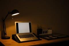 Σκοτεινό εσωτερικό δωματίων με το lap-top και τις συσκευές στον πίνακα στοκ φωτογραφία με δικαίωμα ελεύθερης χρήσης