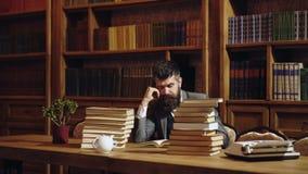 Σοβαρός άνδρας σπουδαστής που διαβάζει ένα βιβλίο σε μια βιβλιοθήκη Άτομο με το βιβλίο ανάγνωσης γενειάδων στο υπόβαθρο ραφιών Άτ φιλμ μικρού μήκους